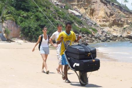 Guia turístico carregando bagagem na Primeira Praia de Morro de São Paulo